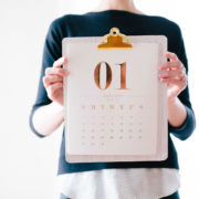 Woman holding clipboard with January calendar