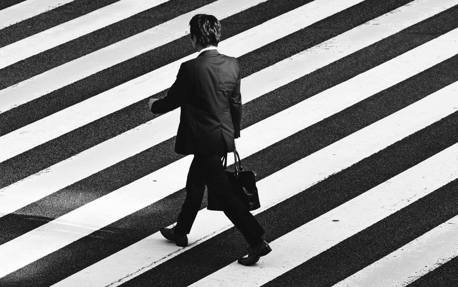 Overhead view of man in suite walking in crosswalk